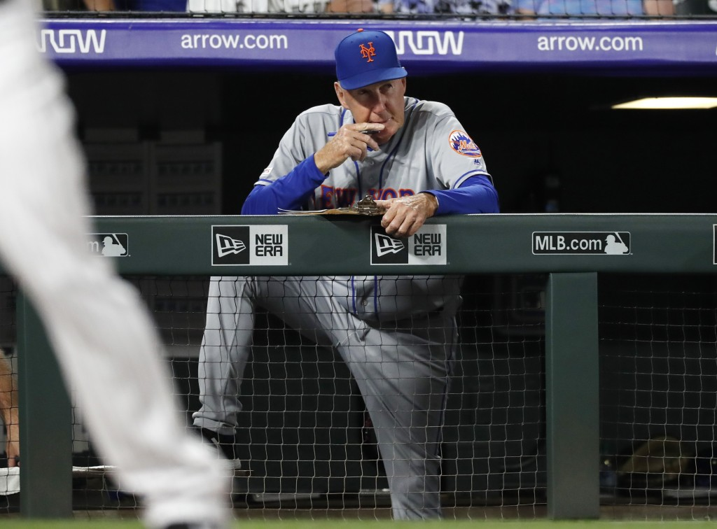 New York Mets interim pitching coach Phil Regan looks on as relief pitcher Walker Lockett works against the Colorado Rockies in the fifth inning of a