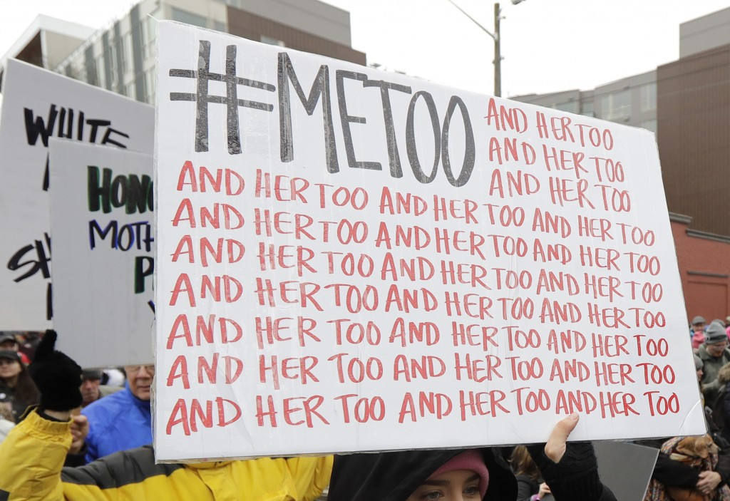 FILE - In this Jan. 20, 2018 file photo, a marcher carries a sign with the popular Twitter hashtag #MeToo used by people speaking out against sexual h...