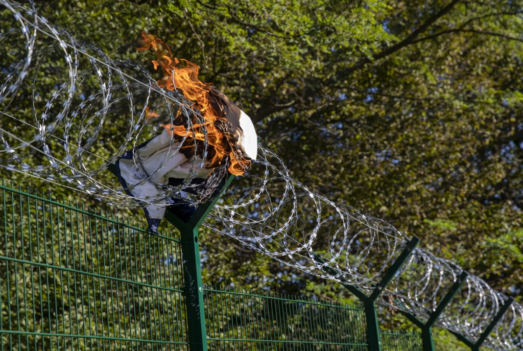 In this Sept. 4, 2019 photo, a jacket left by migrants burns in the razor-wire at the border fence between Croatia and Slovenia in the village of Rado...