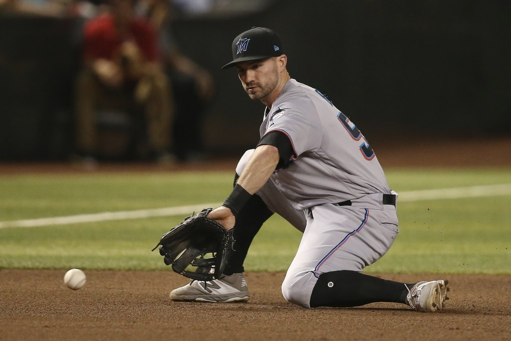 Miami Marlins third baseman Jon Berti gets set to scoop a grounder hit by Arizona Diamondbacks' Nick Ahmed before throwing to first base for the out d...