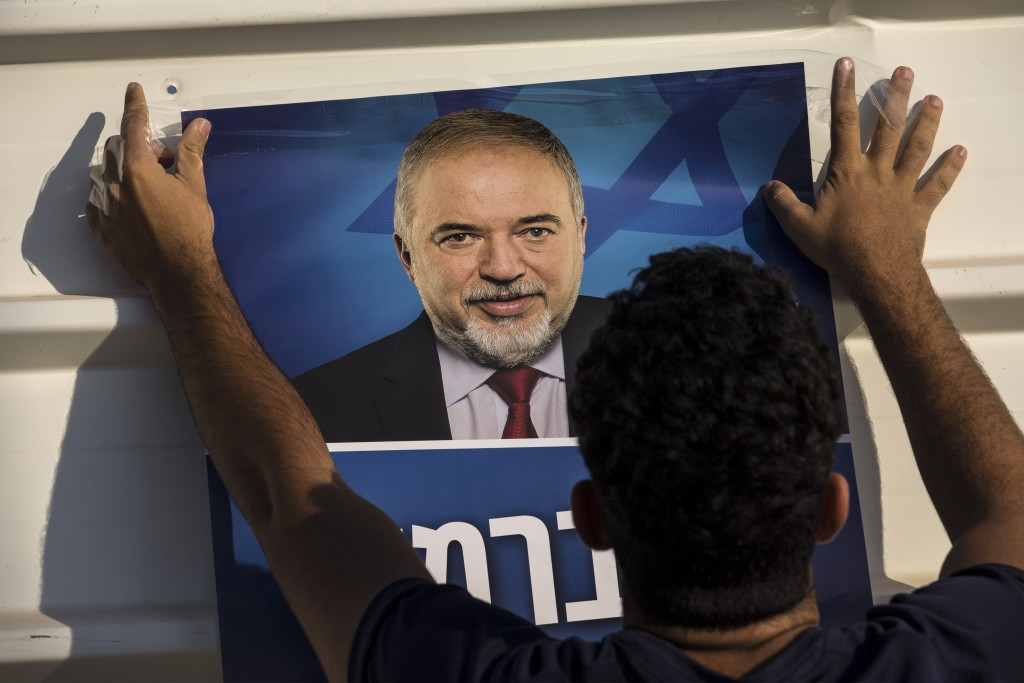 Israeli supporter of the leader of the Yisrael Beiteinu (Israel Our Home) right-wing nationalist party Avigdor Liberman hangs election poster outside