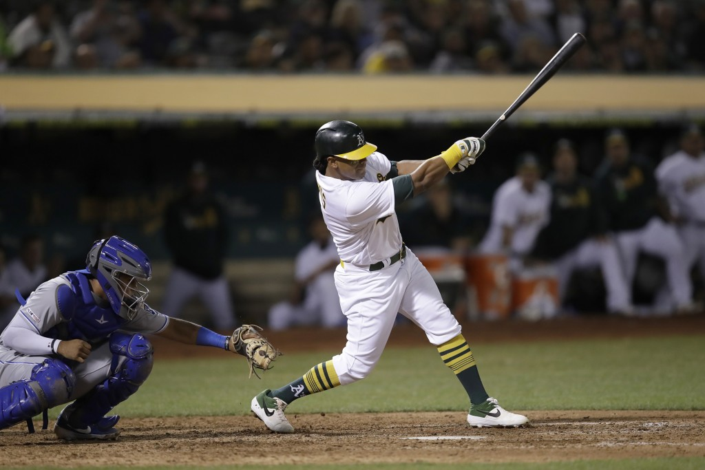 Oakland Athletics' Khris Davis swings for an RBI single off Kansas City Royals' Kevin McCarthy in the eighth inning of a baseball game, Monday, Sept. ...