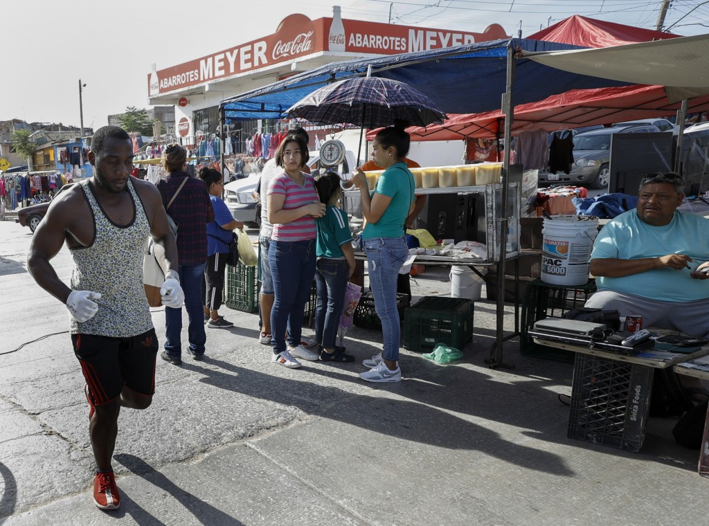 In this July 31, 2019, photo, Alphat, of Uganda runs through a neighborhood surrounding the El Buen Pastor shelter for migrants in Cuidad Juarez, Mexi...
