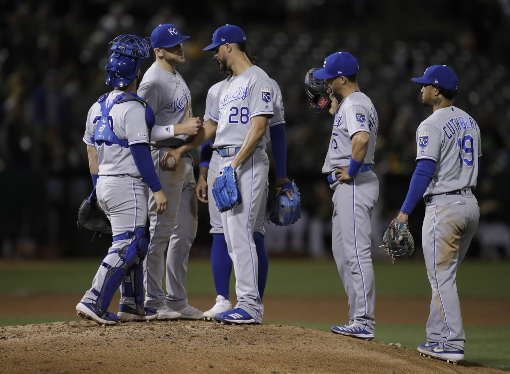 Kansas City Royals pitcher Jorge Lopez (28) speaks with players on the mound as he waits to be removed during the seventh inning of the team's basebal...