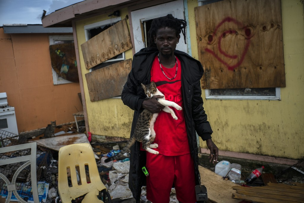 Vladimir Safford, an immigrant from Haiti, poses with his cat next the rubble of his home, in the aftermath of Hurricane Dorian in Abaco, Bahamas, Mon...