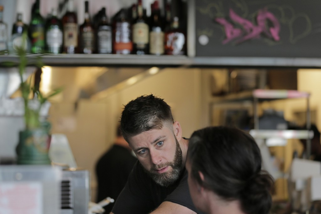In this Thursday, Sept. 12, 2019 photo, Chris Miles helps to prepare his restaurant, Batesy's, for opening in the Rockaway section of New York. Miles