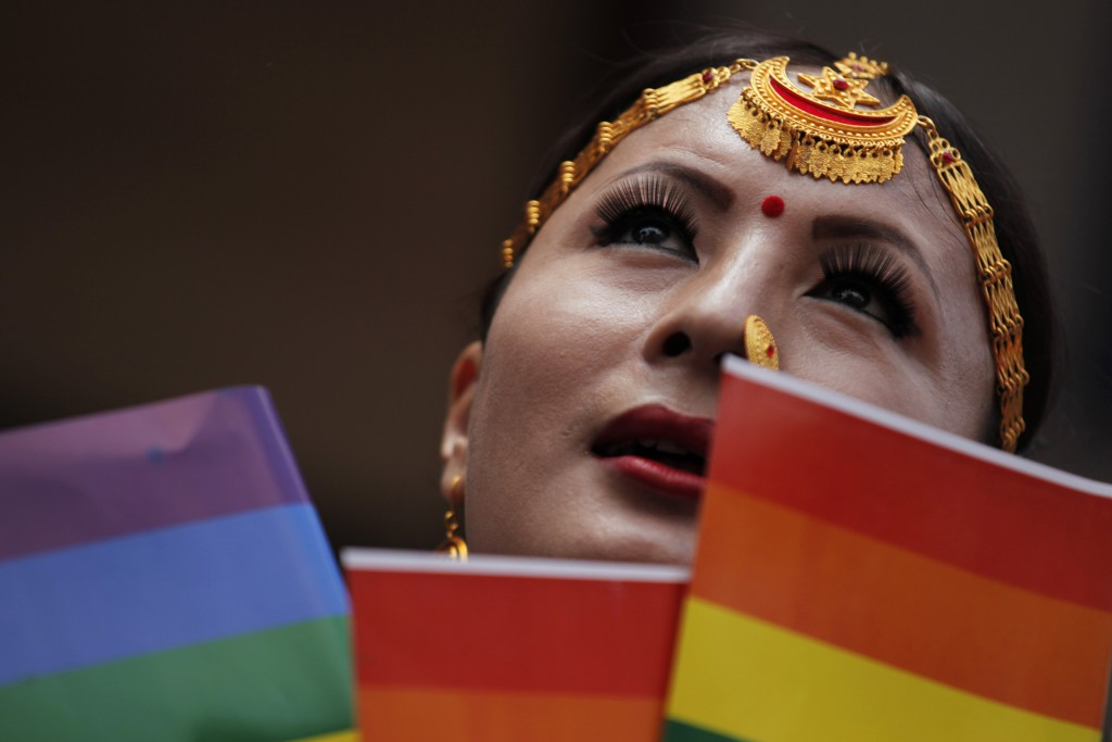 In this Aug. 16, 2019, photo, a participant holds a rainbow flag before marching in a gay pride parade in Kathmandu, Nepal. Nepal seized the lead in e...