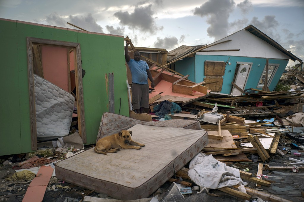 A man stands next to a destroyed house as a dog named Francoise rests on a mattress in the rubble left by Hurricane Dorian in Abaco, Bahamas, Monday, ...