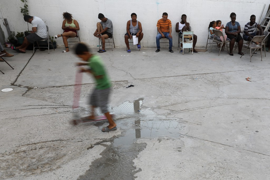 In this July 26, 2019, photo, people from Africa and Central America sit in chairs as the sun sets at El Buen Pastor shelter for migrants in Cuidad Ju...