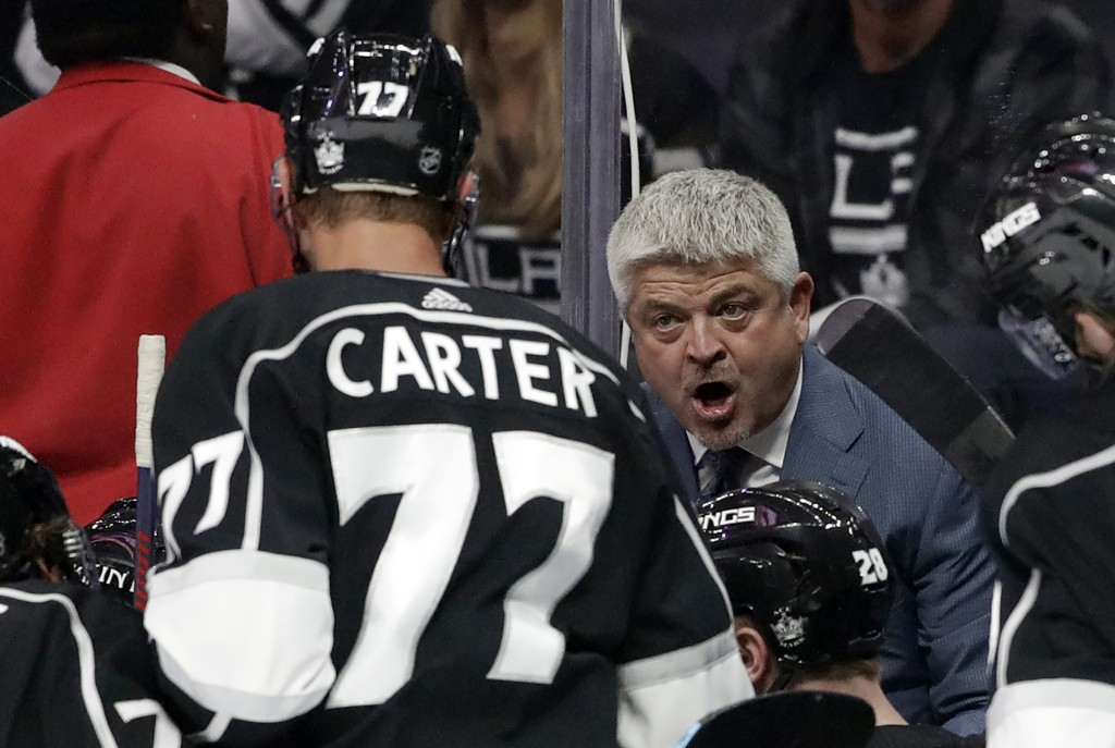 Los Angeles Kings coach Todd McLellan, right, talks to Jeff Carter (77) during the second period of the team's preseason NHL hockey game against the A...
