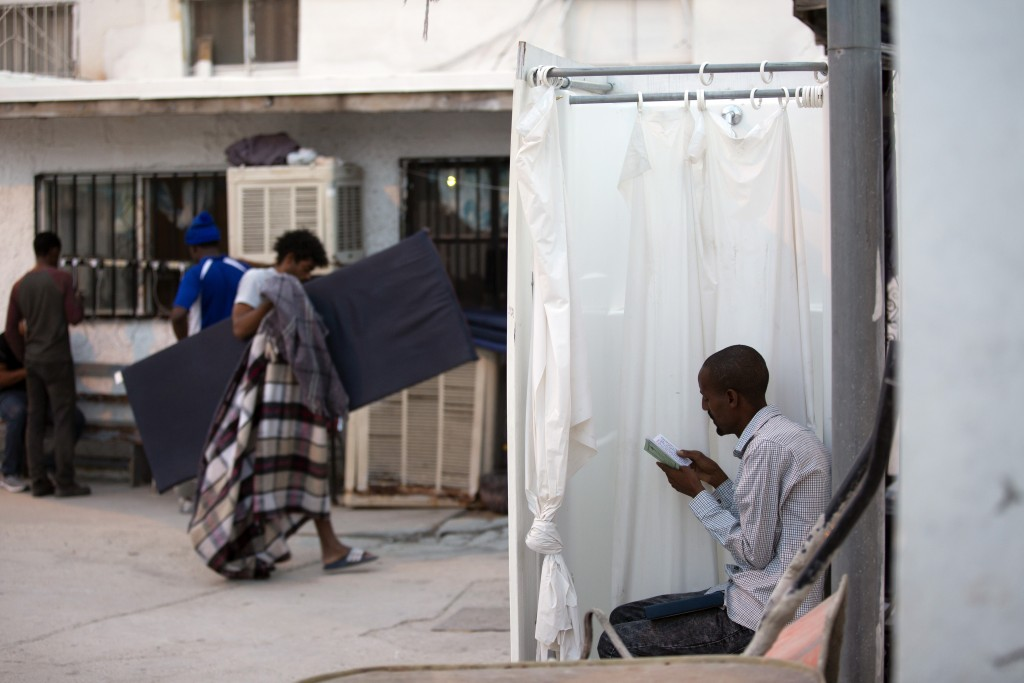 In this July 27, 2019, photo, an Ethiopian man reads his Bible in a shower stall as dawn breaks and others return their mattresses after sleeping outs