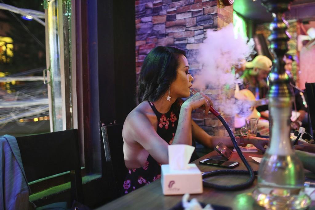 In this Aug. 23, 2019, photo, Meghna Lama smokes hookah at Tiffany restaurant in Thamel, Kathmandu, Nepal. For Lama, who has been running Pink Tiffany...