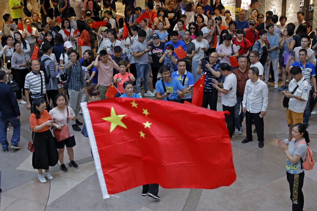 Pro-China supporters wave Chinese national flags in a shopping mall in Hong Kong, Wednesday, Sept. 18, 2019. Activists involved in the pro-democracy p...