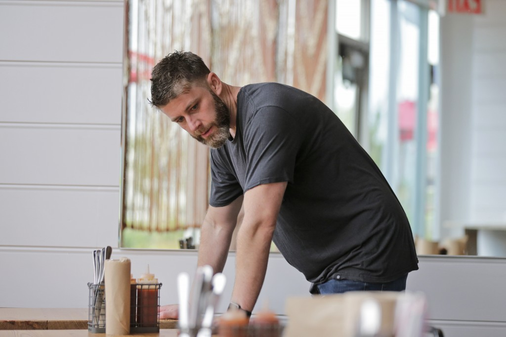 In this Sept. 12, 2019 photo, Chris Miles helps to prepare his restaurant, Batesy's, for opening in the Rockaway section of New York. Miles and his pa