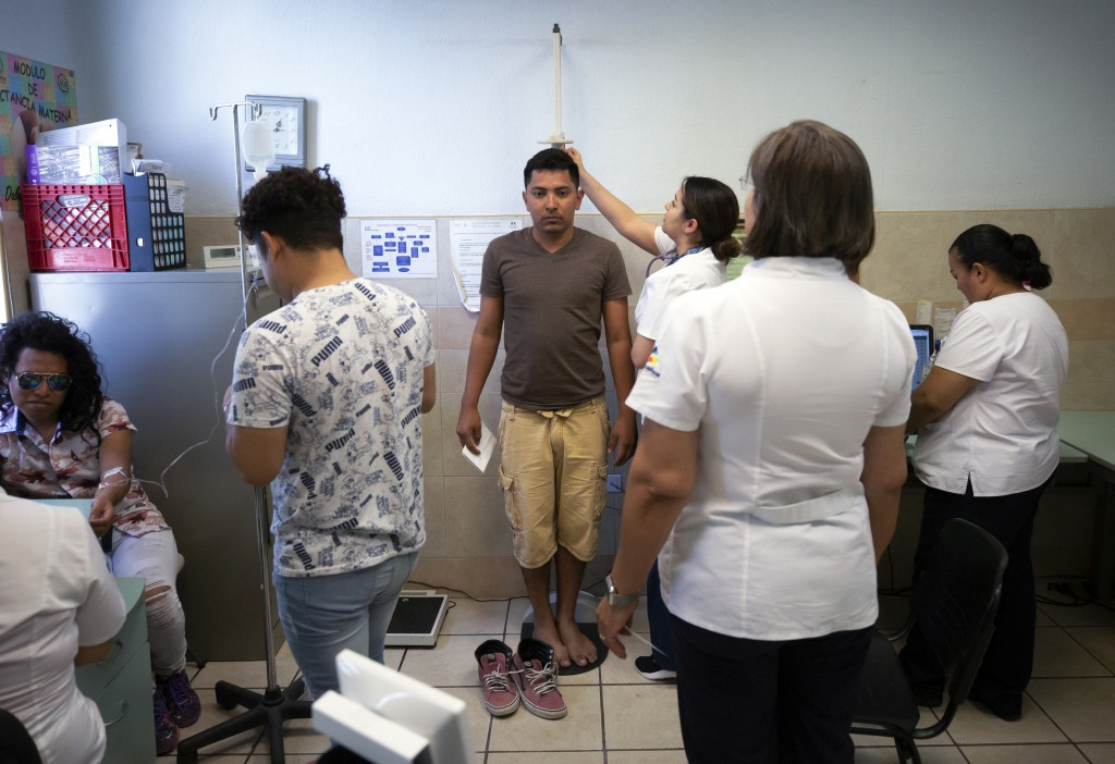 In this July 25, 2019, photo, Samuel, of Honduras, center, is treated at a clinic after taking a bus from El Buen Pastor shelter for migrants in Cuida
