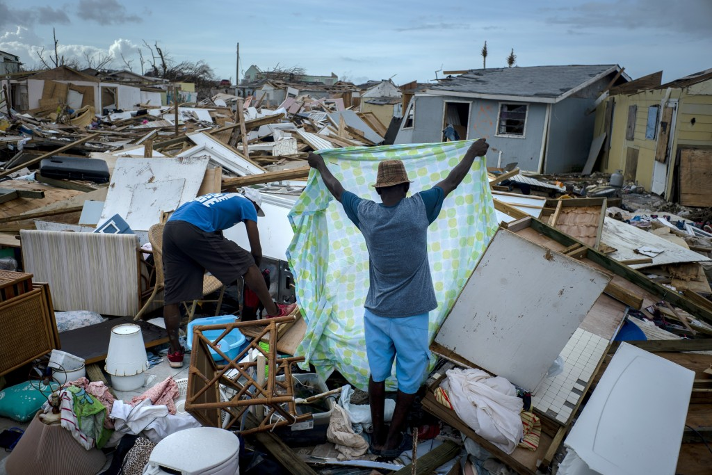 Immigrants from Haiti recover their belongings from the rubble in their destroyed homes, in the aftermath of Hurricane Dorian in Abaco, Bahamas, Monda...