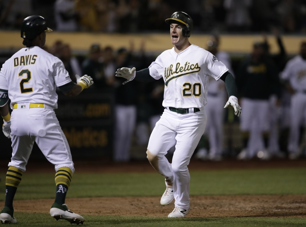 Oakland Athletics' Mark Canha, right, celebrates with Khris Davis (2) after scoring against the Kansas City Royals during the seventh inning of a base...