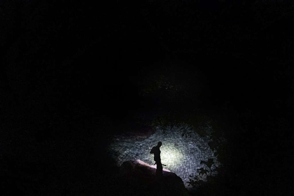 Nicholas Bingham stands at the water's edge before jumping in to go night spearfishing, which is banned, in Stewart Town, Jamaica, Friday, Feb. 15, 20...