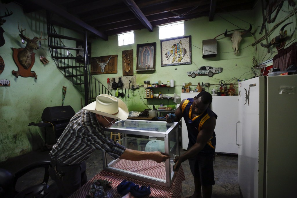In this July 30, 2019, photo, Desidero Ojeda, left, of Texas, works with Alphat, of Uganda in repairing a display case at Ojeda's corner store near El