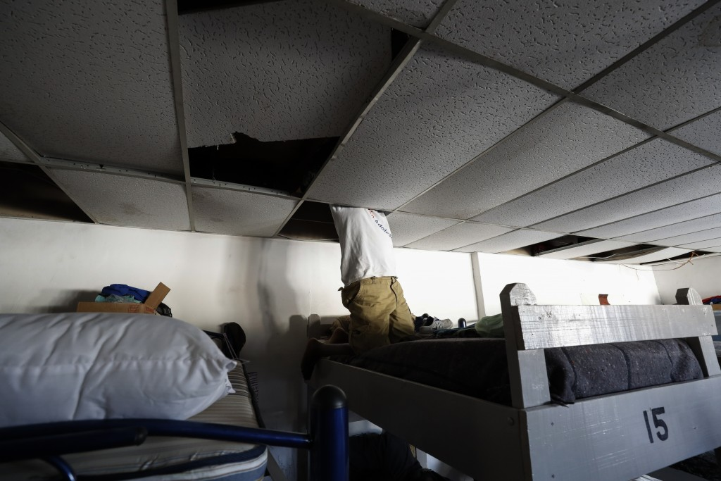 In this July 31, 2019, photo, a man from Africa uses the ceiling space above his bunk to store his valuables at El Buen Pastor shelter for migrants in