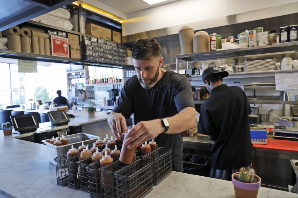 In this Sept. 12, 2019 photo, Chris Miles helps to prepare his restaurant, Batesy's, for opening in the Rockaway section of New York. Miles and partne