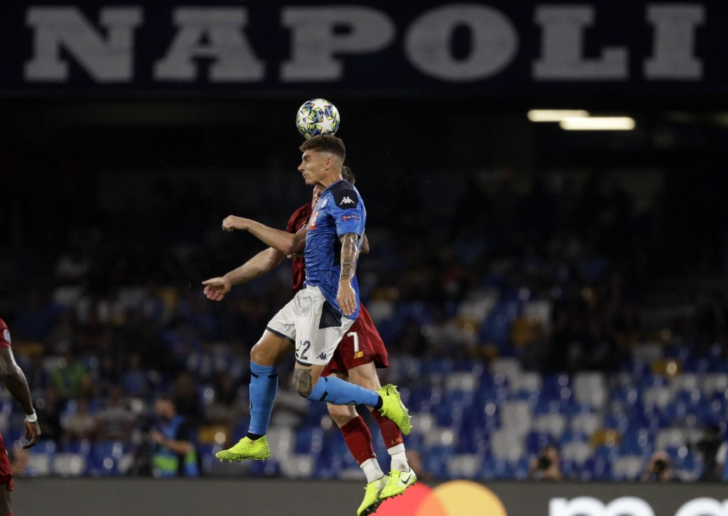 Napoli's Giovanni Di Lorenzo, foreground, and Liverpool's James Milner jump for the ball during the Champions League Group E soccer match between Napo...