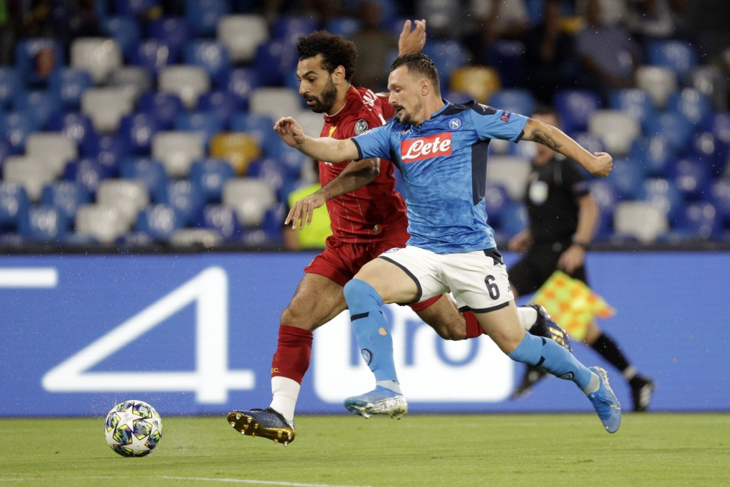 Liverpool's Mohamed Salah, left, and Napoli's Mario Rui fight for the ball during the Champions League Group E soccer match between Napoli and Liverpo