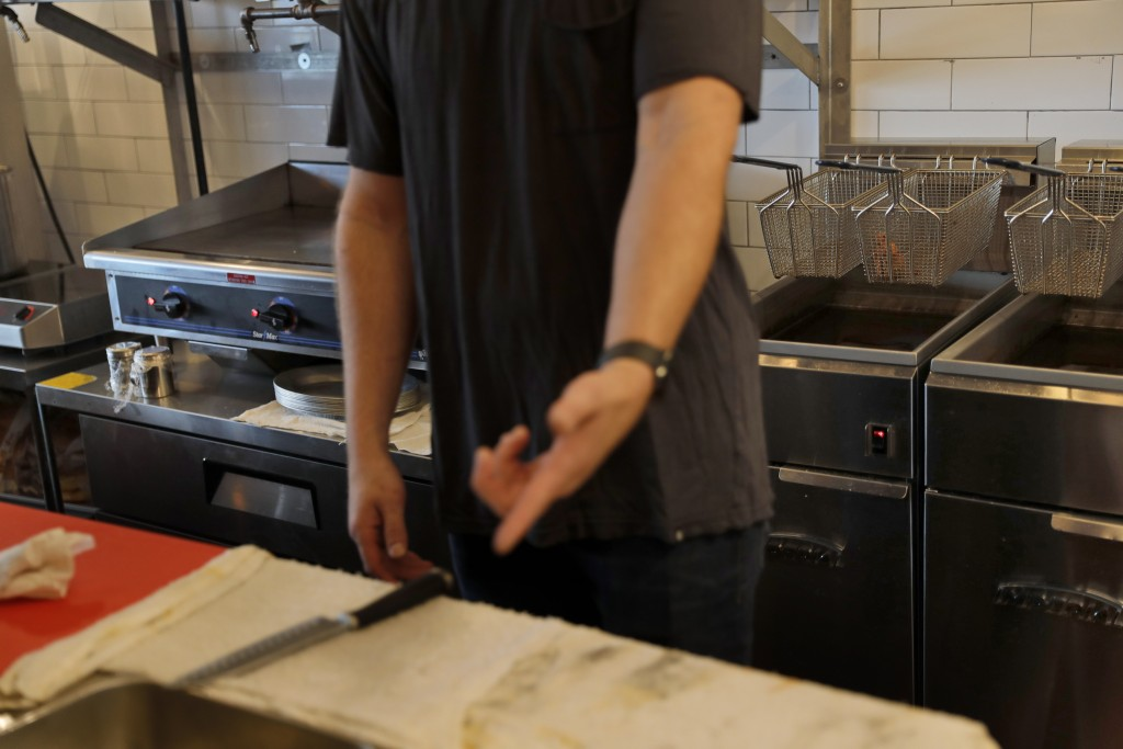 In this Thursday, Sept. 12, 2019 photo, Chris Miles points out some electric appliances at his restaurant, Batesy's, in the Rockaway section of New Yo...