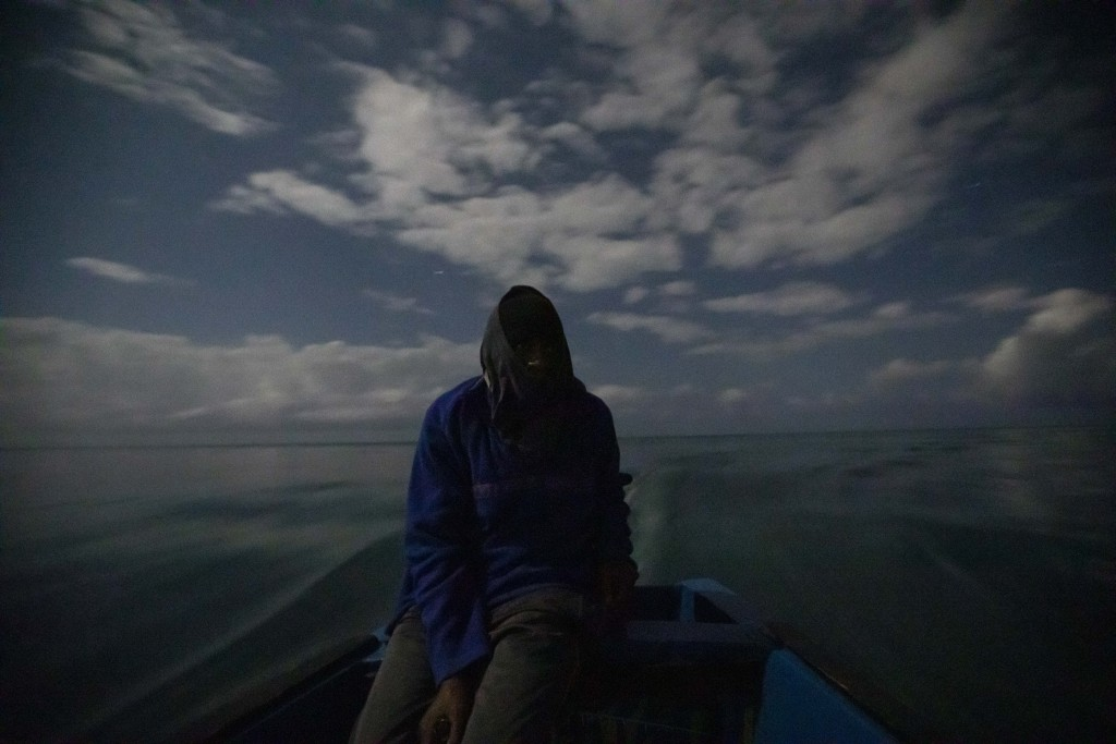 White River Fish Sanctuary warden Mark Lobban steers the boat under moonlight while patrolling the no-take zone for illegal fishermen in Ocho Rios, Ja...