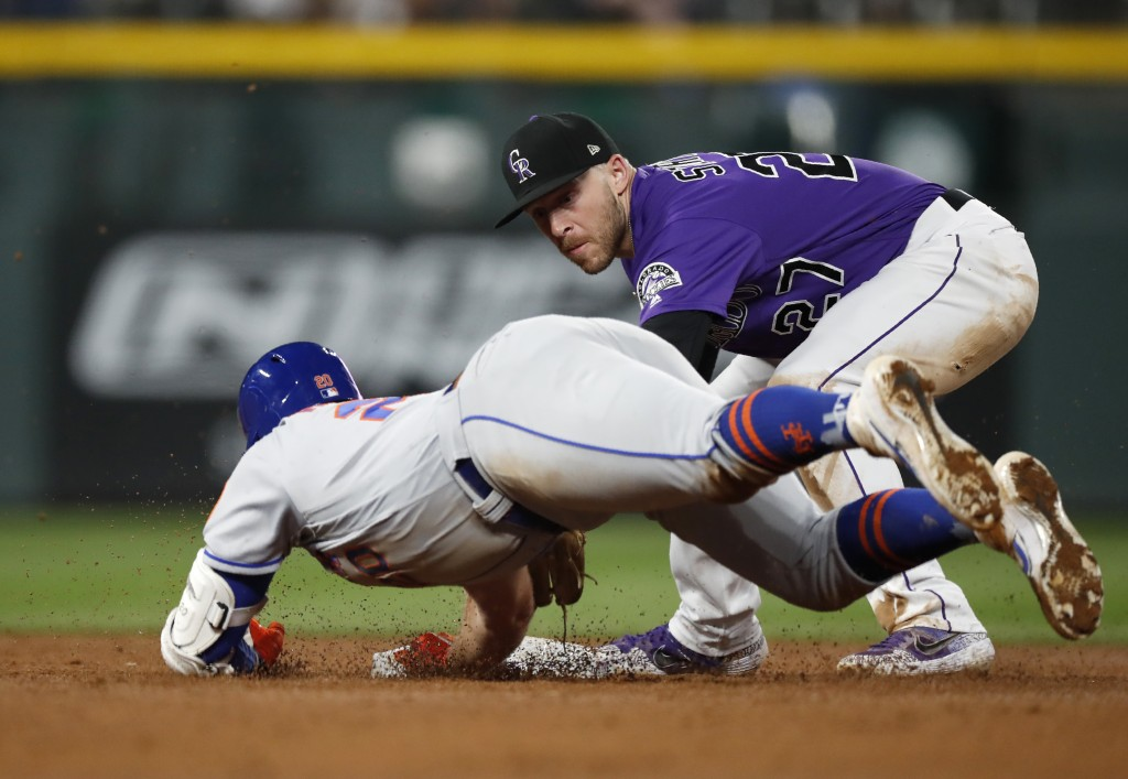Colorado Rockies shortstop Trevor Story, back, tags out New York Mets' Pete Alonso as he slides into second base while trying to stretch a single into