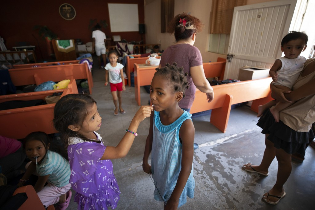 In this July 25, 2019, photo, a Honduran girl shares a lollipop with an African girl at El Buen Pastor shelter for migrants in Cuidad Juarez, Mexico.
