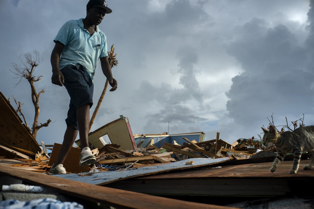 Jesner Merxius, an immigrant from Haiti, walks through the rubble in the aftermath of Hurricane Dorian in Abaco, Bahamas, Monday, Sept. 16, 2019. Dori...