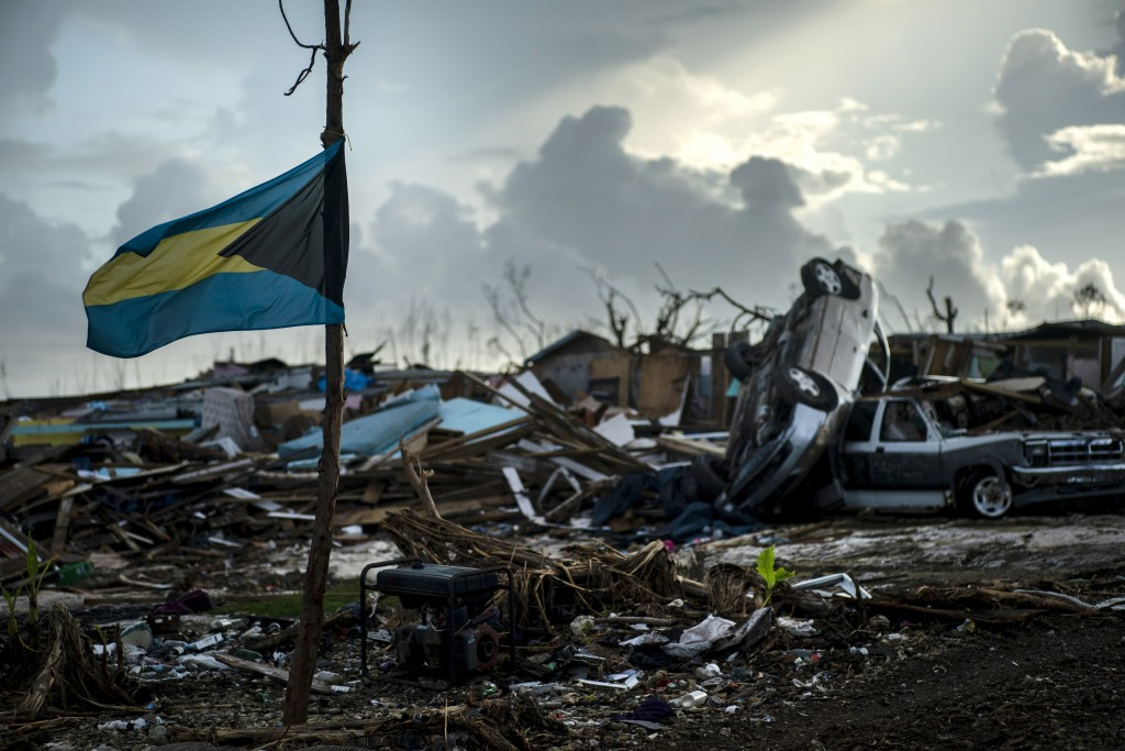 A Bahamas flag flies tied to a sapling, amidst the rubble left by Hurricane Dorian in Abaco, Bahamas, Monday, Sept. 16, 2019. Dorian hit the northern ...
