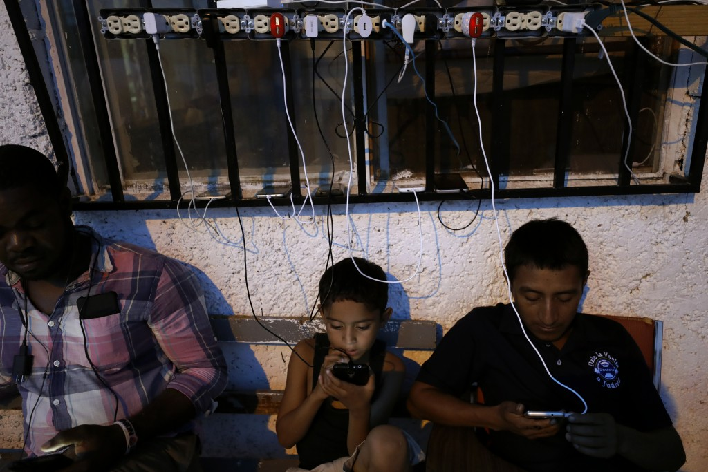 In this July 30, 2019, photo, migrants from Africa and Latin America check their phones among cables of charging phones plugged into sockets at El Bue...