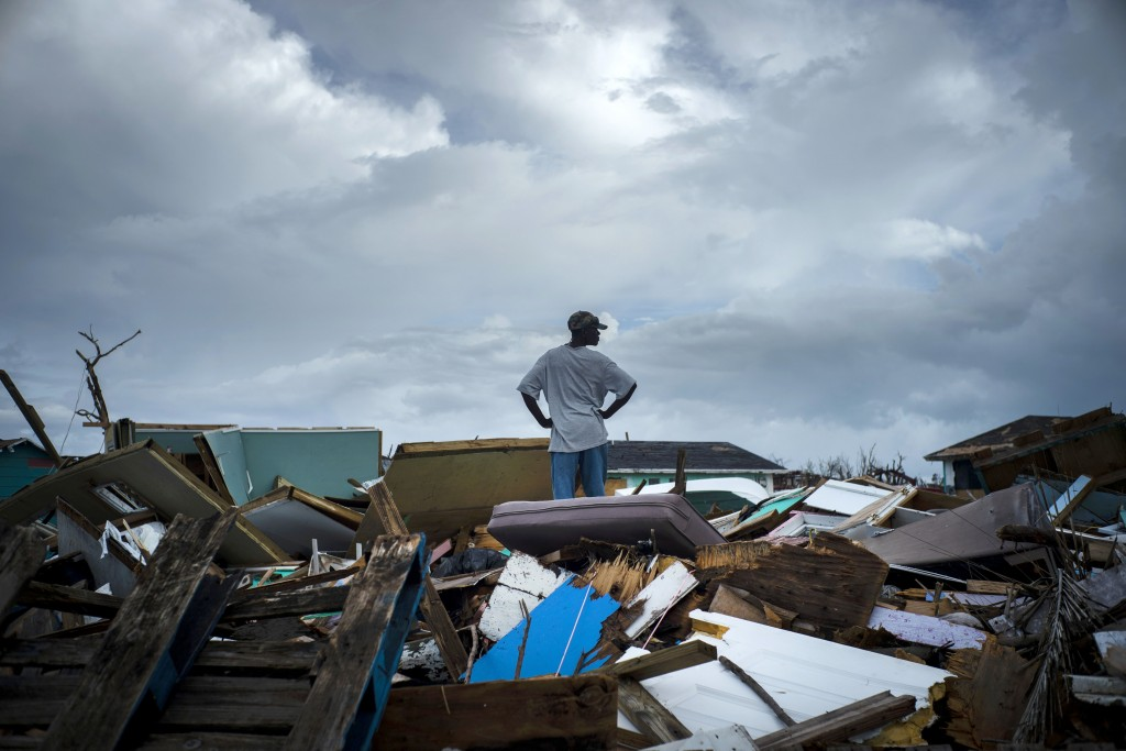 A man stands on the rubble of his home in the Haitian Quarter, after the passage of the Hurricane Dorian in Abaco, Bahamas, Monday, Sept. 16, 2019. Do...