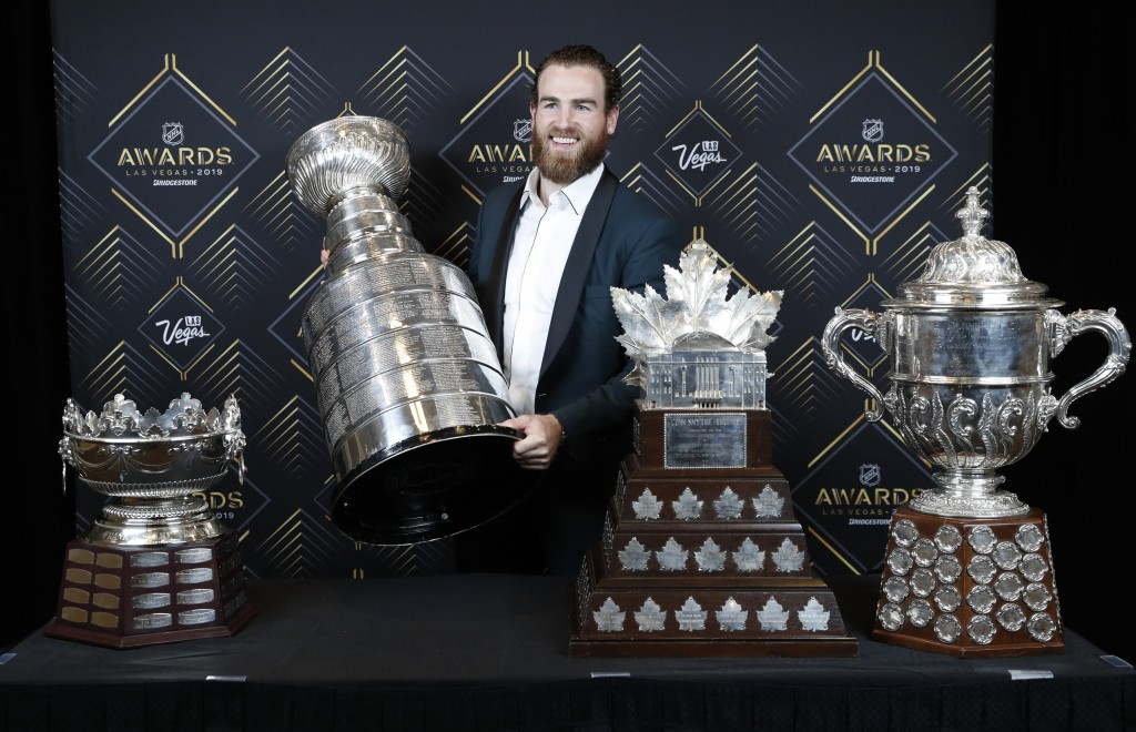 FILE - In this June 19, 2019, file photo, St. Louis Blues' Ryan O'Reilly poses with, from left, the Frank J. Selke Trophy, for top defensive forward; ...
