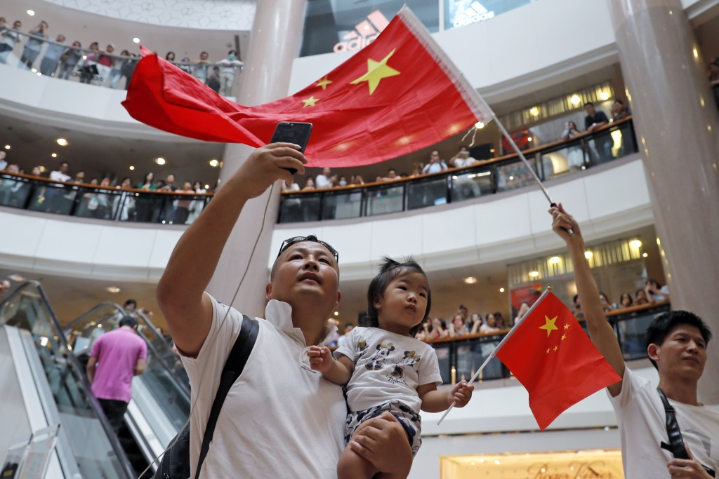 Pro-China supporters wave Chinese national flag in a shopping mall in Hong Kong, Wednesday, Sept. 18, 2019. Activists involved in the pro-democracy pr