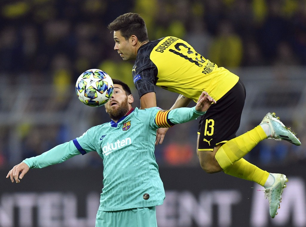 Barcelona's Lionel Messi, left, fights for the ball with Dortmund's Raphael Guerreiro during the Champions League Group F soccer match between Borussi
