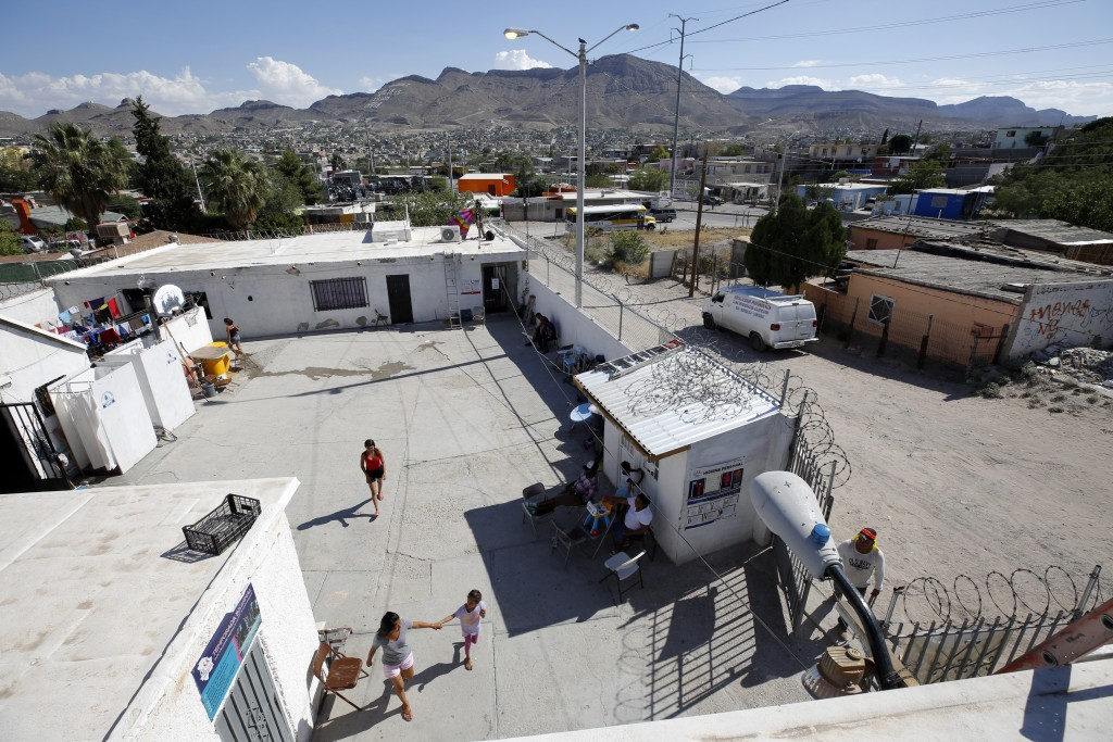 In this July 30, 2019, photo, people walk through the patio at El Buen Pastor shelter for migrants in Cuidad Juarez, Mexico. (AP Photo/Gregory Bull)