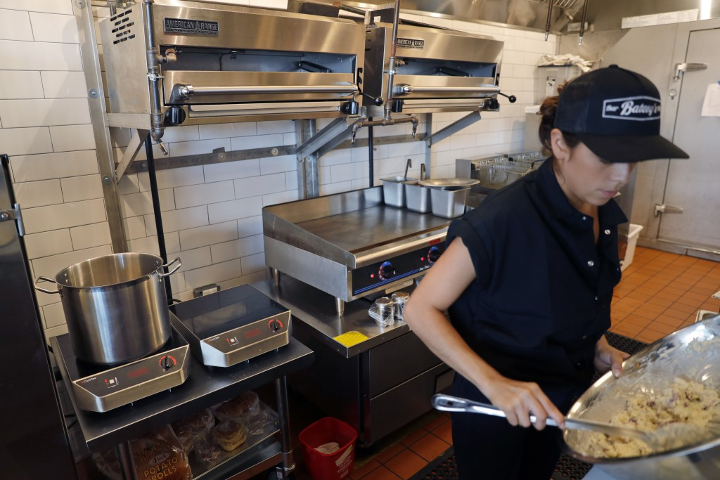 In this Thursday, Sept. 12, 2019 photo, primarily electric appliances line the kitchen of Batesy's restaurant in the Rockaway section of New York. Bus