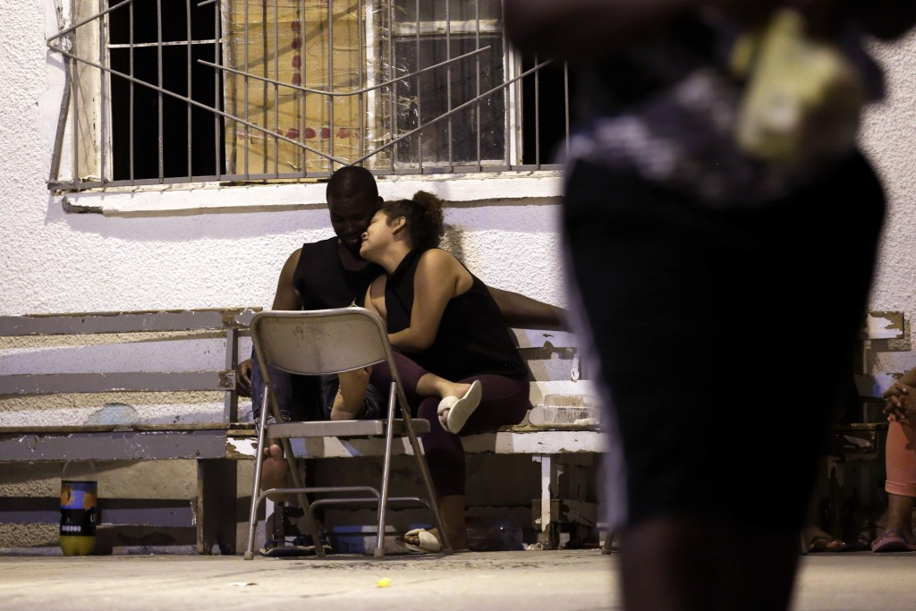In this July 28, 2019, photo, a woman from Nicaragua embraces a man from Africa under the patio floodlights at El Buen Pastor shelter for migrants in