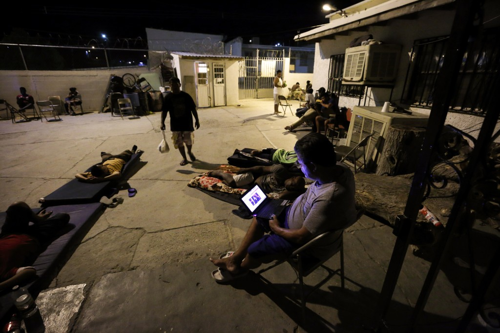 In this July 25, 2019, photo, a Cuban man looks at a computer screen as others lay around the patio at El Buen Pastor shelter for migrants in Cuidad J