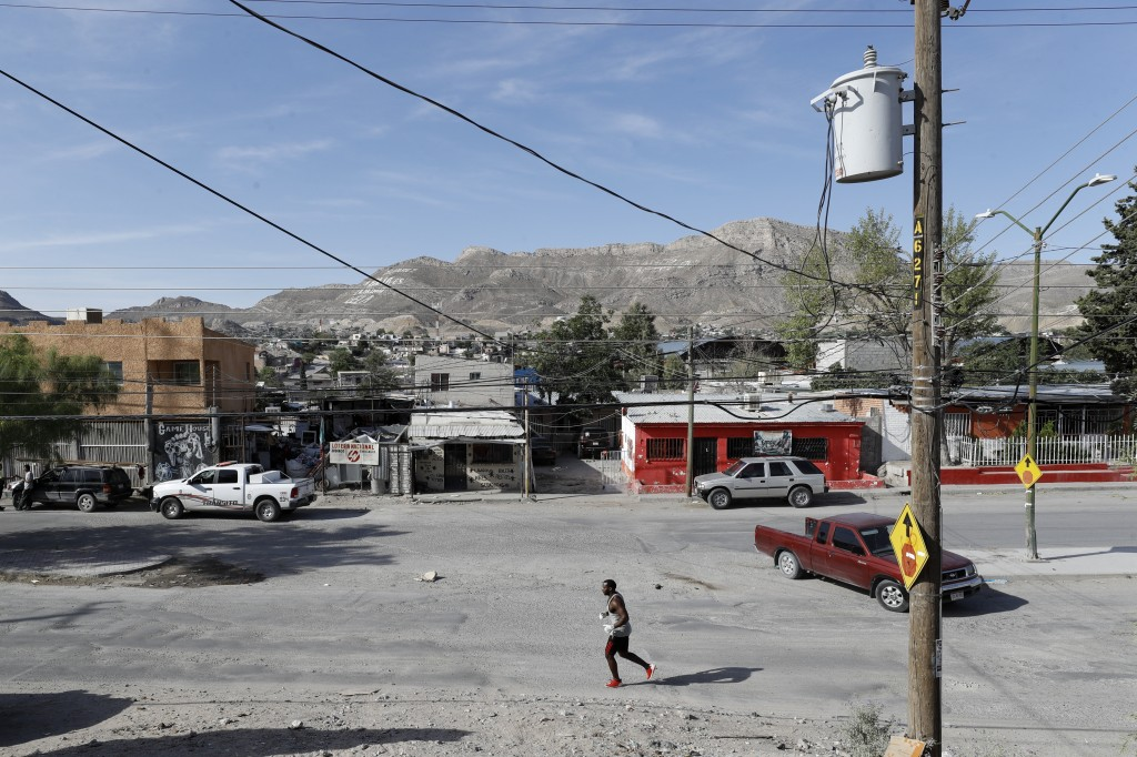 In this July 31, 2019, photo, Alphat, of Uganda, runs through a neighborhood surrounding the El Buen Pastor shelter for migrants in Cuidad Juarez, Mex...