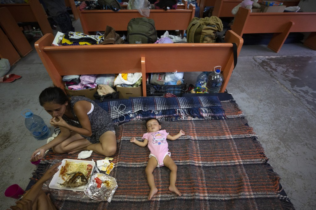 In this July 28, 2019, photo, Evelyn, of El Salvador, eats a shared lunch as her daughter sleeps an area set up for families among the pews at El Buen...