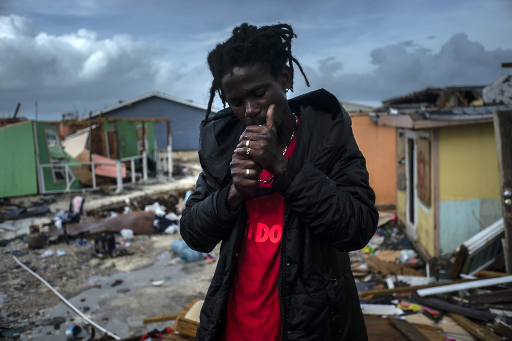 Vladimir Safford, an immigrant from Haiti, lights a cigarette next to the rubble if his home, in the aftermath of Hurricane Dorian, in Abaco, Bahamas,...