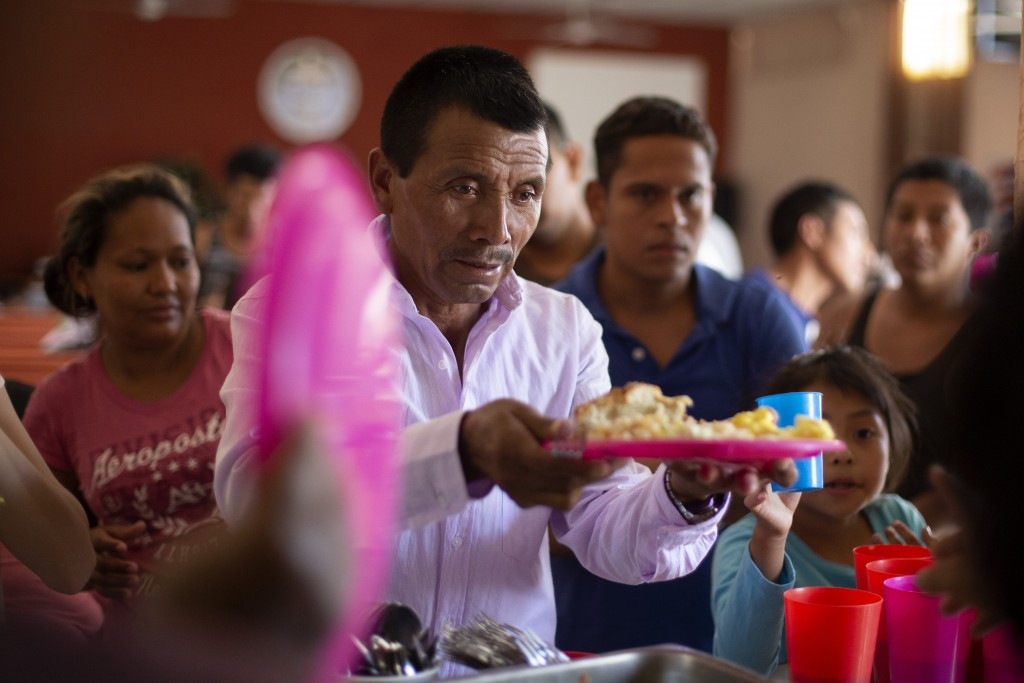 In this July 25, 2019, photo, a Guatemalan man gets a plate of food at El Buen Pastor shelter for migrants in Cuidad Juarez, Mexico. (AP Photo/Gregory