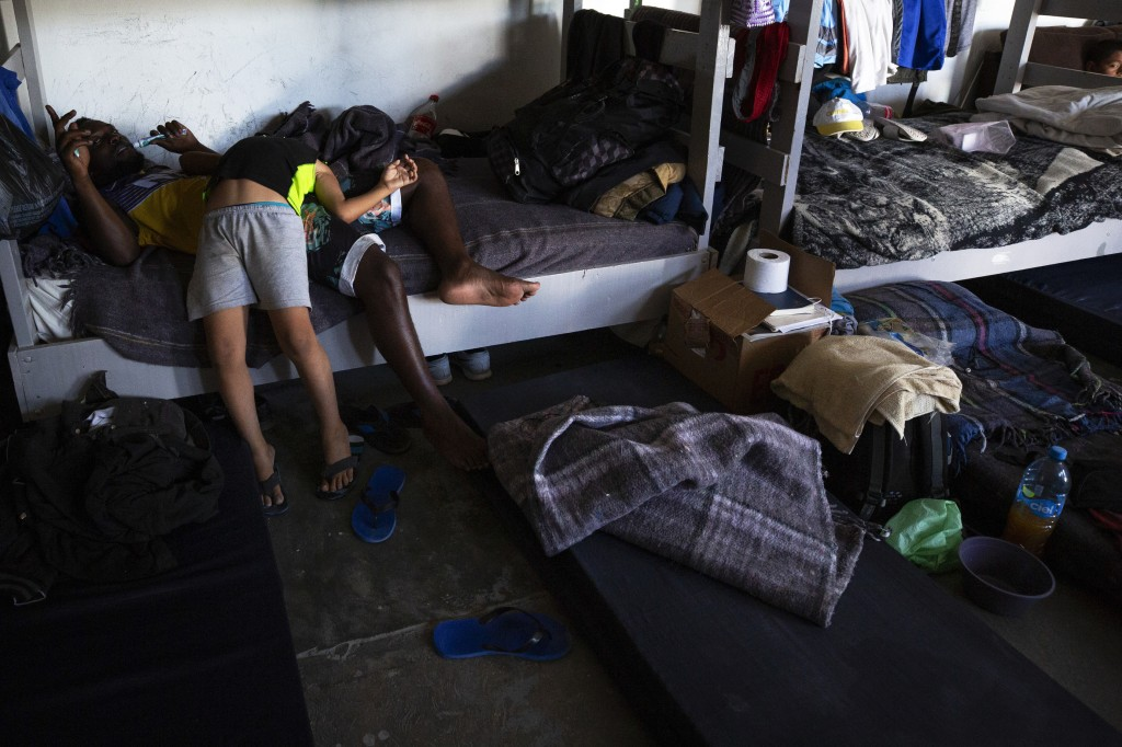 In this July 25, 2019, photo, a boy from Honduras jokes with an African man in the dormitory at El Buen Pastor shelter for migrants in Cuidad Juarez,