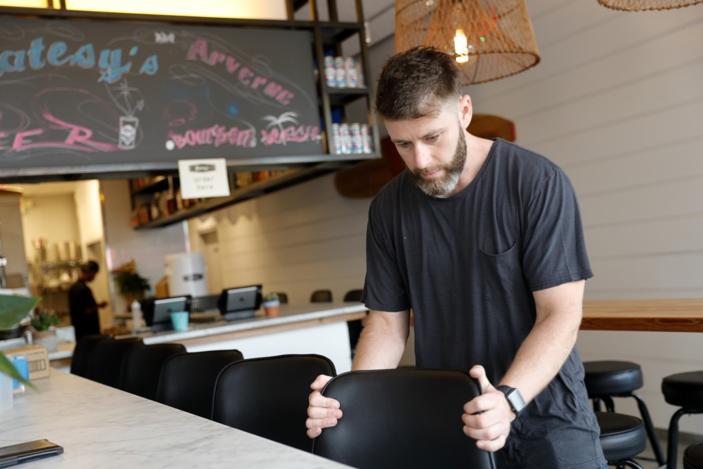 In this Thursday, Sept. 12, 2019 photo, Chris Miles helps to prepare his restaurant, Batesy's, for opening in the Rockaway section of New York. Busine