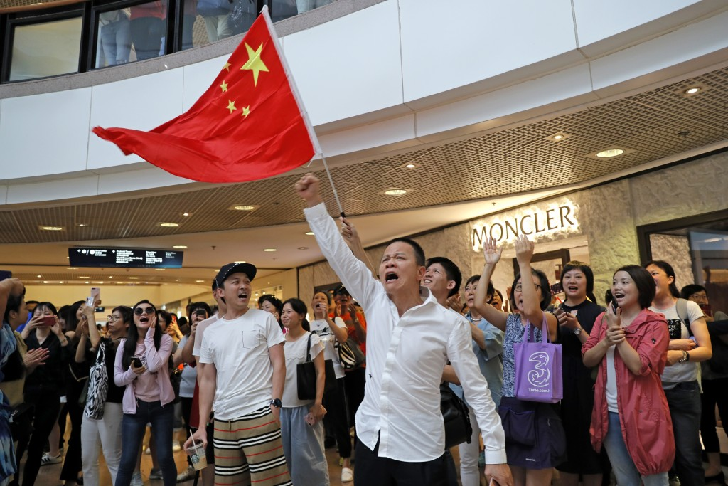 Pro-China supporters wave a Chinese national flag in a shopping mall in Hong Kong, Wednesday, Sept. 18, 2019. Activists involved in the pro-democracy