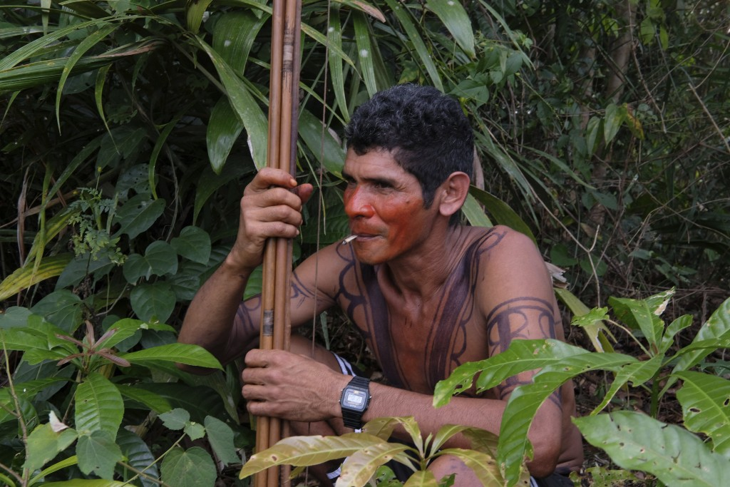 Luiz Tembe, an indigenous Tembe warrior, smokes a cigarette as he waits for police to arrive with other members of his tribe on the Alto Rio Guama ind...
